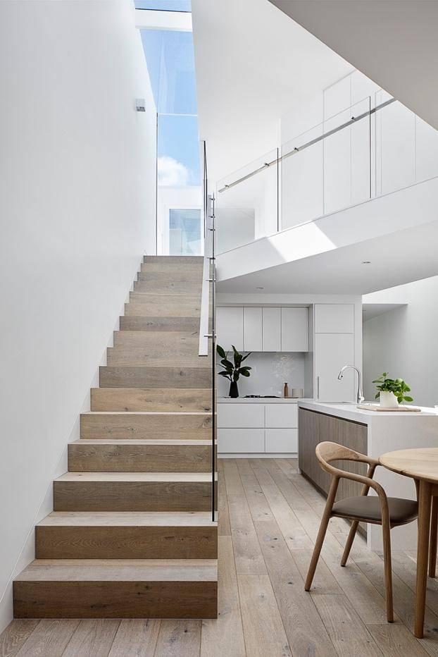 Những bậc cầu thang gỗ dẫn lên tầng trên với phần chiếu nghỉ được lắp kính giúp gia chủ có thể nhìn ra khoảng trời trong xanh phía sau nhà. Thiết kế này giúp căn nhà như được nới rộng và gần gũi hơn với thiên nhiên.